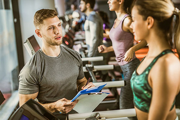 personal trainer helping client workout on a treadmill