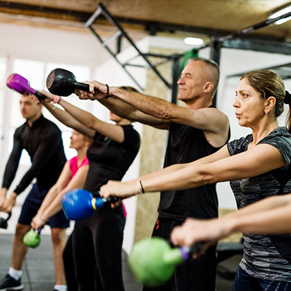 group of people training together in a gym with kettlebells